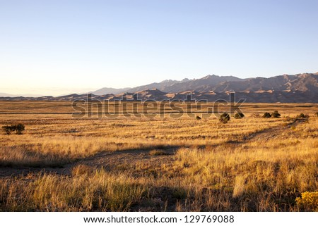 Grasslands at sunset with the Great Colorado Sand Dunes in the distance - stock photo