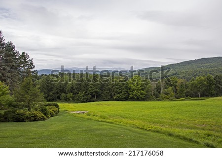 Grassy field in Vermont with mountains and trees in background - stock photo