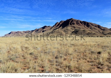 Grassy Savannah with mountains in background, Namib Naukluft Park. Namibia