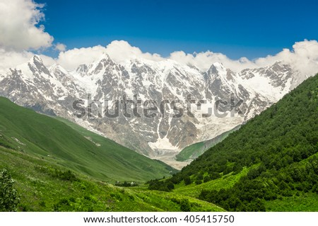 Grassy valley and snow-capped mountains in Georgia (Svaneti)
