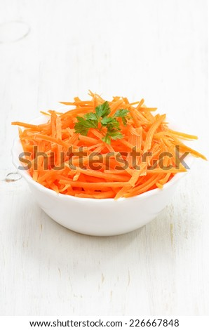Grated carrot in bowl on white wooden table - stock photo