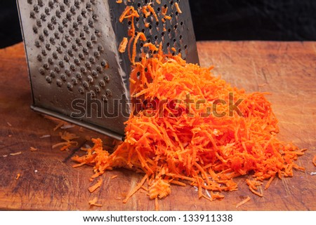 Grated carrot on a wooden plate - stock photo