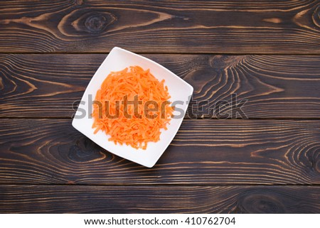 grated carrot plate on dark wooden table. flat lay - stock photo