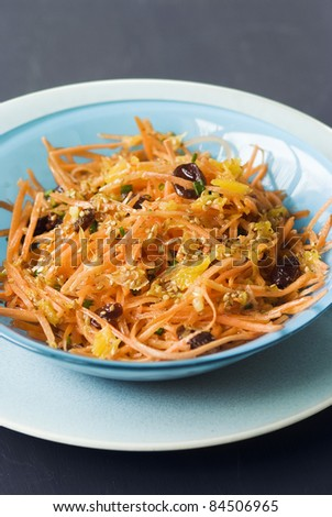 Grated carrot salad with raisins and sesame seeds - stock photo