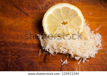 Grated celery and a lemon on a wooden plate - stock photo