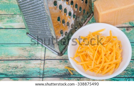 Grated cheddar cheese and a steel grater over wooden background - stock photo