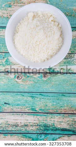 Grated cheese in white bowl over wooden background - stock photo