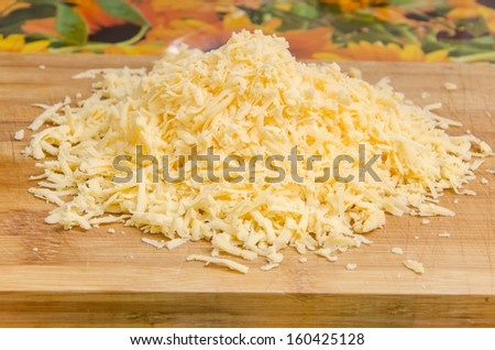 Grated cheese on a cutting board - stock photo
