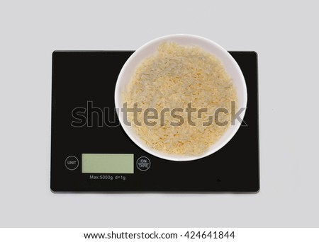 Grated cheese on a digital white kitchen scale. (weighing products) - stock photo