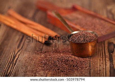 grated dark chocolate in copper measure pan on wooden background