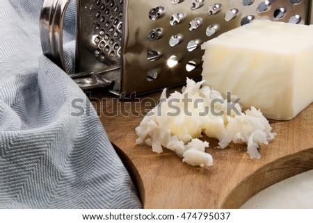 grated lard and grater on a wooden board