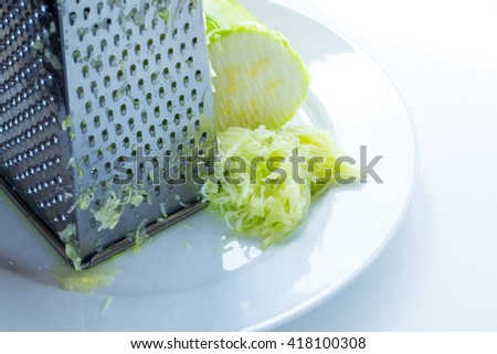 grated marrow on a white plate and a grater for vegetables