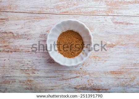 Grated nutmeg in a bowl on wooden table - stock photo