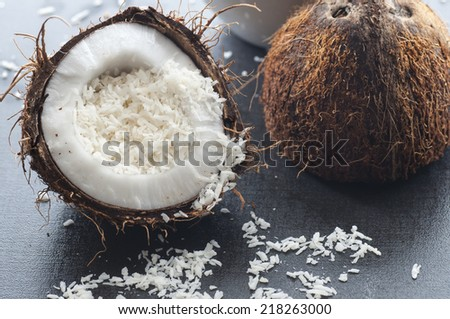 Grated organic coconut in a half fresh coconut. - stock photo