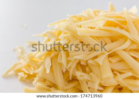 Grated yellow cheese on white - stock photo
