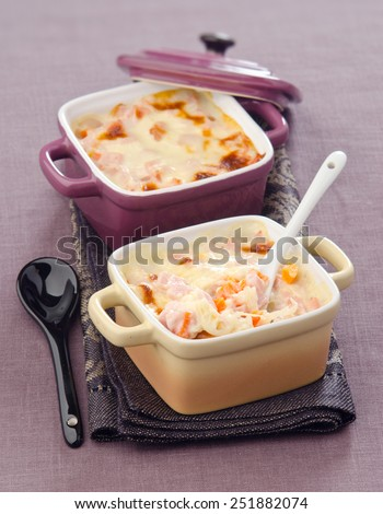 Gratin of rice and ham in a ceramic cocotte on a napkin - stock photo
