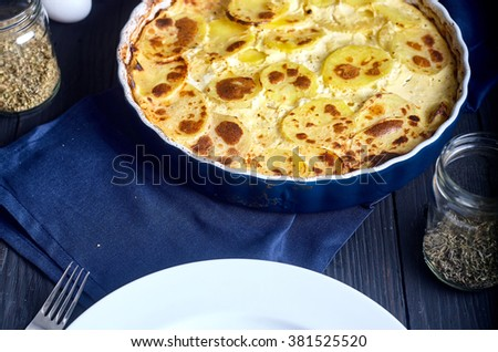 Gratin potatoes roasted with cream, eggs and cheese in ceramic blue dish. Dark wood background and spices in jars near it - stock photo