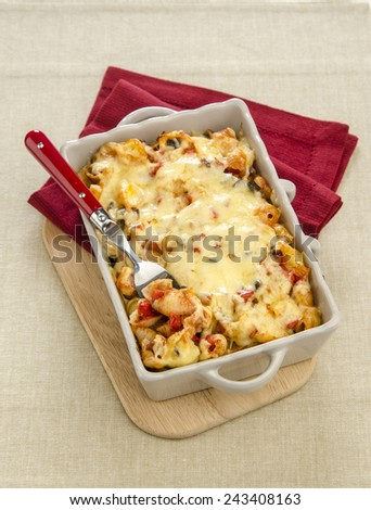 gratin with cheese and ketchup in a gray plate on a wooden stand with red cloth