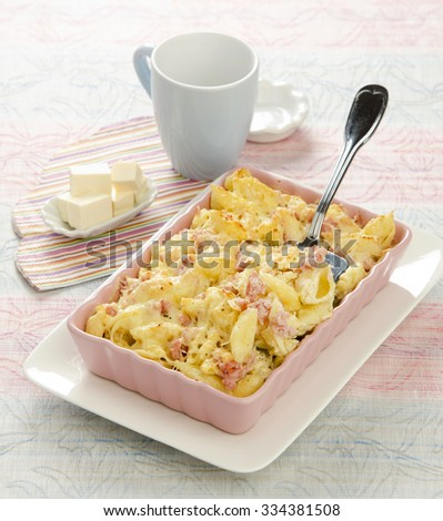 Gratin with pasta and bacon cheese baked in a ceramic pink form - stock photo