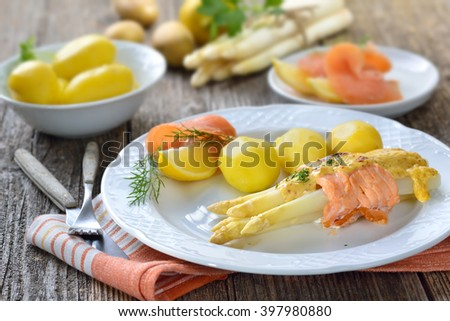Gratinated white asparagus with smoked salmon and cheese sauce, served with boiled potatoes and lemon - stock photo