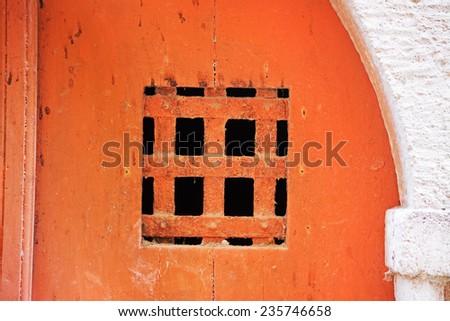 grating in an old orange door. Shot in Bosa, Italy - stock photo