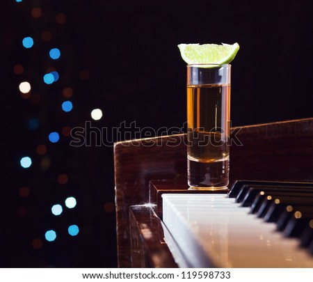 Gratitude for the maestro, glass with tequila on a piano.