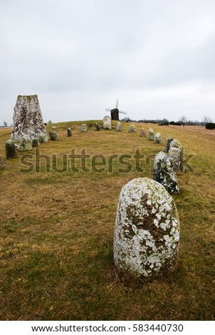 Grave field with a stone ship and an old wooden windmill at the Swedish island Oland in the Baltic Sea
