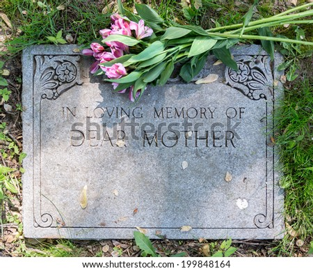 Grave marker in cemetery with flowers for concept of death and loss - stock photo