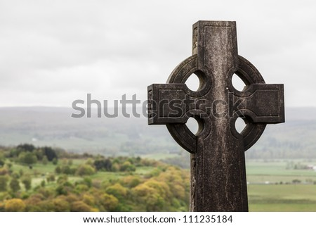 Grave stone on a graveyard looking over a valley - stock photo