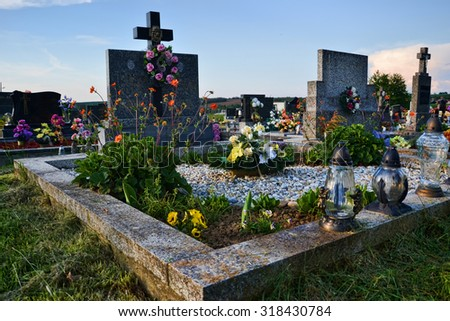 Grave / tombstone in the cemetery / graveyard. All Saints Day / All Hallows / 1st November. Flowers and candles on tomb stone in churchyard. Slovakia, Europe - stock photo