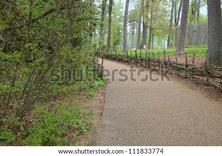 gravel path with stick fence - stock photo