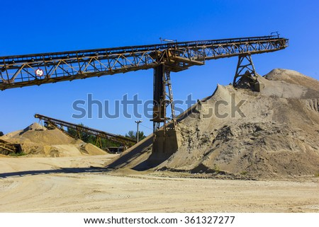 gravel pit with an industrial gravel sorter machinery and clear blue sky