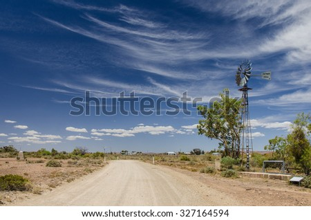 Gravel road and water pump windmill in outback town on cloudy day - stock photo