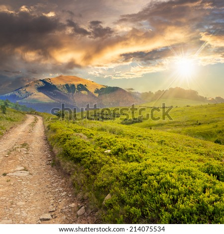 gravel road going off into the distance and passes through the green field in mountains at sunset