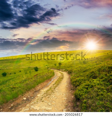 gravel road going on hillside to highlands at sunset with rainbow