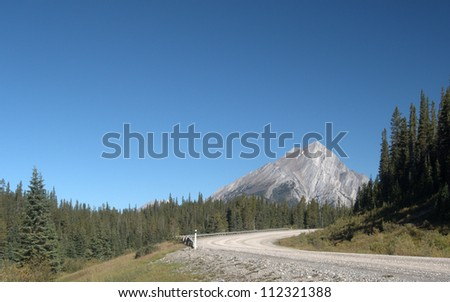 Gravel Road leading into the mountains.  Spray Lakes Road looking north, Kananaskis Country, Alberta Canada - stock photo