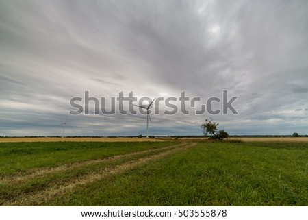 Gravel road on green field and windmill in background