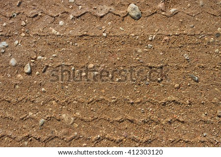 Gravel road surface with a print of a plurality of wheels.