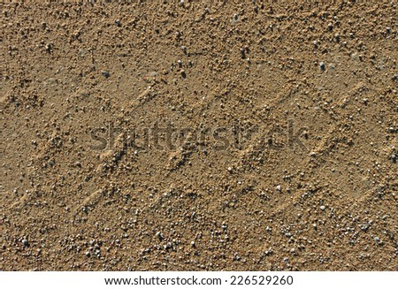 Gravel road surface with trail of wheel. - stock photo