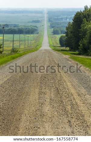 Gravel road through the flat prairies with field and trees across the landscape - stock photo