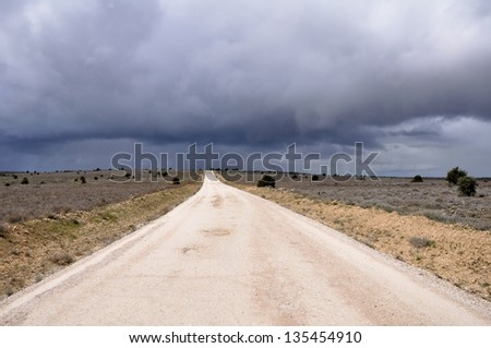Gravel road with storm clouds