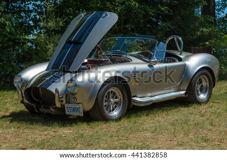 Gravenhurst, Ontario - June 18, 2016: Classic Ford Cobra 427 car in a silver metallic finish, is parked on grassy area with an open hood - stock photo