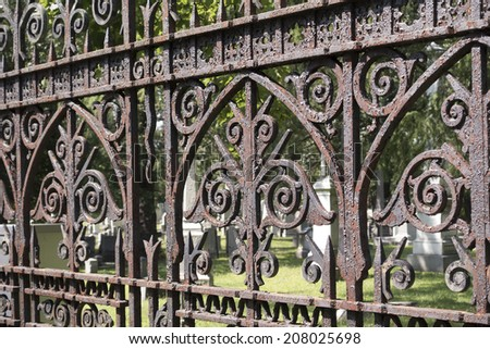 graves behind rusted ornate fence - stock photo