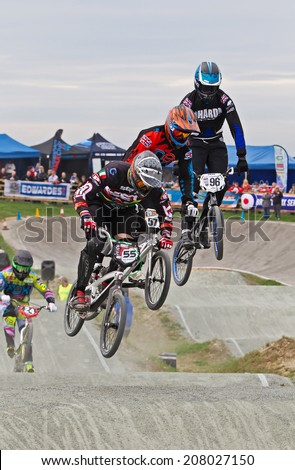 GRAVESEND, UK - APRIL 12: Riders competing in the elite class of the UK National BMX champs at the Kent cyclopark negotiate the rollers section during the final race on April 12, 2014 in Gravesend  - stock photo
