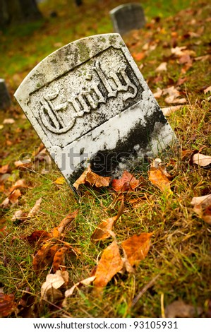 """Gravestone in an old cemetery during autumn which reads, """"Emily"""". - stock photo"""