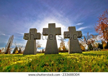 Graveyard three crosses on green meadow silhouette view - stock photo