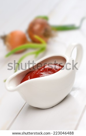 Gravy boat on white wooden plank table - stock photo