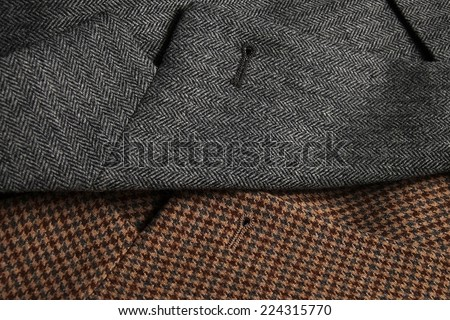 Gray and brown classic woolen tweed coats side-by-side, showing lapels detail - stock photo