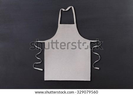 Gray apron on chalkboard vintage background  - stock photo