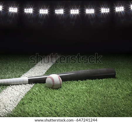 Gray baseball bat and ball on field with white stripe and stadium lights